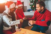 Merry Christmas And Happy New Year. Nice Picture Of Family Preparing Gifts Together. Girl And Young  poster