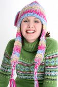Beautiful teen girl with dazzling smile in green sweater and crazy winter hat.  Shot in studio over