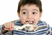 Close up of a two year old boy eating possum pie with a big silver spoon.  Shot in studio over white