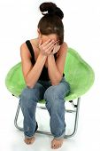 Young woman barefoot in jeans sitting in bright green chair with hands over face.  Shot in studio ov