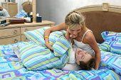 Madre e hijo tener cosquillas luchan en casa en la cama.