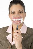 stock photo of lip augmentation  - Beautiful Hispanic business woman with magnifying glass in front of mouth - JPG