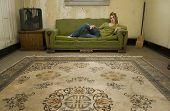 Beautiful Hispanic woman sitting in impoverished apartment.