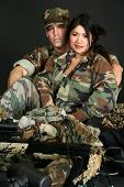 Attractive 30 something couple in military fatigues.
