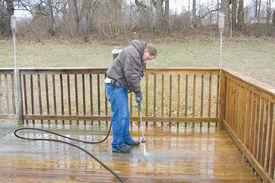 stock photo of pressure-wash  - Worker pressure washing deck on rear of house - JPG