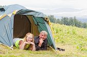 Happy pair in tent against mountains