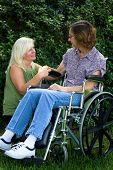 picture of crippled  - Caregiver tries to comfort an elderly disabled woman in a wheelchair - JPG