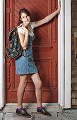 lächelnd Teenager-Mädchen mit Rucksack lehnt sich gegen alte rote Tür.