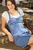 Smiling Teenage Girl In Denim Dress With Backpack Beside Her.