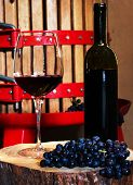 picture of wine-press  - Still life with glass of red wine and vintage wine press in the background - JPG
