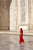 Woman walking past the Taj in a sari.