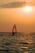 Silhouette Of A Windsurfer On A Gulf On A Sunset