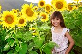Closeup Smiling Girl In The Sunflowers Field