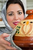 Traditional Moroccan immigrant woman in Europe cooking tajine during Ramadan in her modern kitchen