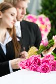 stock photo of casket  - Mourning man and woman on funeral with pink rose standing at casket or coffin - JPG