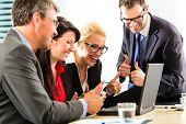 Geschäft - Bildschirm vier Profis im Büro in Geschäftskleidung looking at Laptop arbeiten zusammen