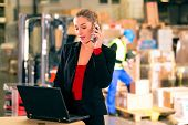Friendly Woman, dispatcher or supervisor using cell phone and laptop at warehouse of forwarding comp