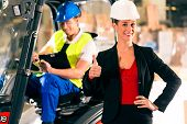 Forklift driver and female super visor with clipboard at warehouse of freight forwarding company - t