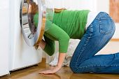 stock photo of laundry  - Young woman or housekeeper has a laundry day at home - JPG