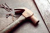 stock photo of nail-cutter  - Construction tools background composed by saw nails and an hammer - JPG