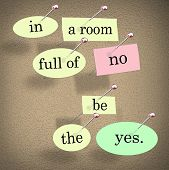 The words In a Room Full of No Be the Yes saying pinned on a bulletin board