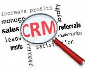 A magnifying glass hovering over several sales related words and focuses on CRM - which stands for customer relationship management