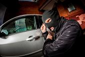 stock photo of scum  - Robber and the car thief in a mask opens the door of the car and hijacks the car - JPG