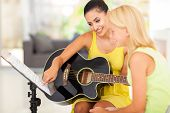 pretty music teacher tutoring young girl to play guitar