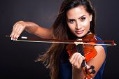 stock photo of hair bow  - attractive young woman playing violin on black background - JPG