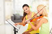 preteen girl play violin under music teacher's instructions