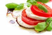 Caprese Salad. Tomato and Mozzarella slices with basil leaves. Over white background