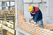 image of bricklayer  - construction mason worker bricklayer installing red brick with trowel putty knife outdoors - JPG