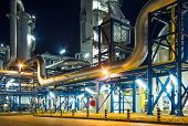 stock photo of pipeline  - pumps and piping system inside of industrial plant at night - JPG
