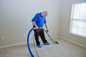 foto of house cleaning  - Man treating carpet with commercial cleaning chemicals to help remove stains in carpet - JPG