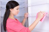 Beautiful young woman washing fridge in kitchen