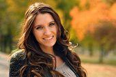 Portrait of smiling brunette girl a autumnal park