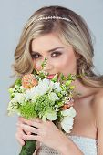 Portrait of a beautiful blond bride with a diamante headpiece. Hair in loose curly style. Wearing se