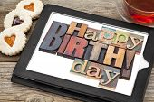 Happy birthday in letterpress wood type on digital tablet with stylus a cup of teat and heart cookie