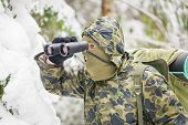 Hunter with binoculars in forest in the winter