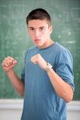 Highschool student in boxing stance in schoolroom