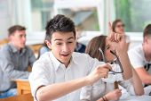 Joyful highschool boy celebrating in classroom