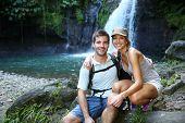 Trekkers reaching waterfall in natural landscape