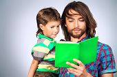 Happy father reading a book to his adorable son.
