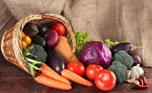 stock photo of sackcloth  - Different vegetables in basket on table on sackcloth background - JPG
