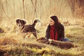 girl with pariah dogs sit in yellow grass warm winter day retro colors