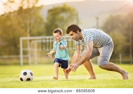 Father and son playing football poster
