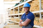 happy african industrial worker standing at building material warehouse