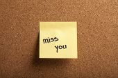 stock photo of miss you  - Color shot of a cork board with a sticky note reading  - JPG