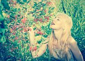 The young beautiful girl near to a bush of a red currant.with a retro effect