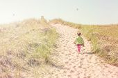 Girls walking up a dune path to the lake